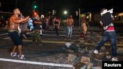 Demonstran yang sebagian besar dari warga kulit hitam, berusaha memblokade jalan di Ferguson, Missouri (17/8).
