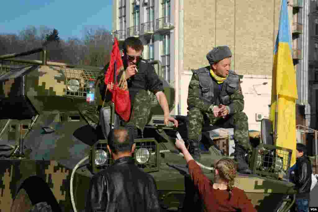 Two men sit atop an armored personnel carrier in downtown Kyiv. (Steve Herman/VOA)