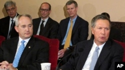 Ohio Gov. John Kasich, front right, and Ohio Senate President Keith Faber, front left, both Republicans, discuss the state budget, June 26, 2015, at the Statehouse in Columbus, Ohio. Ohio is resuming executions using a three-drug combination.