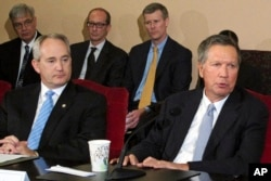 FILE – Ohio Gov. John Kasich, front right, and Ohio Senate President Keith Faber, front left, both Republicans, discuss the state budget, June 26, 2015, at the Statehouse in Columbus, Ohio. Ohio says it will resume executions using a three-drug combination.