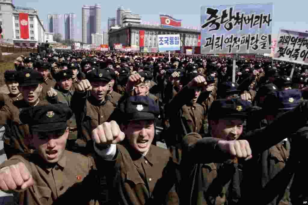 University students punch the air as they march through Kim Il Sung Square in downtown Pyongyang, North Korea, March 29, 2013.