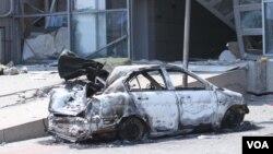 天津爆炸事故现场,核心爆炸区周围多座居民楼窗户被震碎,高速公路桥梁受损,多辆大货车被炸翻,小汽车起火或被砸,多名当地居民仍逗留在事故现场。(美国之音东方拍摄)