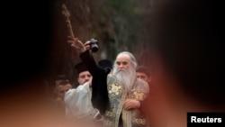 Arhiva - Mitropolit Amfilohije Radović, među vjernicima, baca drveni krst u rijeku Ribnicu tokom proslave Bogojavljanja, u Podgorici, 19. januara 2013. (Rojters)