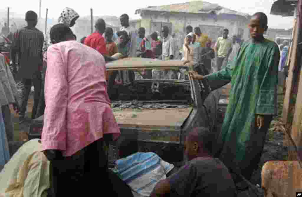 People look at a burnt car after a blast at Gombomru local market on Monday, in Nigeria's northern city Maiduguri February 7, 2012.