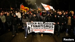 """Participants take part in a demonstration called by anti-immigration group PEGIDA, a German abbreviation for """"Patriotic Europeans against the Islamization of the West"""", in Dresden, Jan. 5, 2015. The text reads: 'Against religious fanatism and any kind of radicalism. Together against violence.'"""