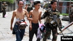 Government soldiers escort residents who were taken hostage and used as human shields by Muslim rebels of Moro National Liberation Front (MNLF) during fighting with government soldiers, in Zamboanga city in southern Philippines, Sept. 17, 2013.