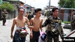 Binh sĩ hộ tống người dân bị phiến quân bắt làm con tin và sử dụng làm lá chắn sống trong thành phố Zamboanga ở miền nam Philippines, ngày 17/9/2013.