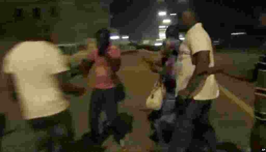 Un policier éloigne des civils de l'hôtel Splendid, à Ouagadougou, le 15 janvier 2016. (AP Television via AP)