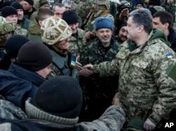 Ukrainian President Petro Poroshenko, right, shakes hands with Ukrainian servicemen in the town of Artemivsk, Ukraine, Feb. 18, 2015.