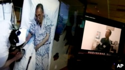 Video clips of China's jailed Nobel Peace laureate Liu Xiaobo, left, as he lays on a bed at a hospital and, right, Liu saying wardens are taking good care of him, are displayed on a computer screen in Beijing, June 29, 2017.