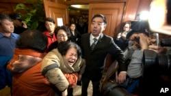 失踪马航班机一名中国乘客的亲属在北京听到最新消息后失声痛哭并瘫倒。(2014年3月24日)