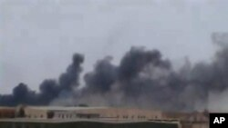 This image taken March 16, 2011 from amateur video and obtained March 17, 2011 shows a plume of smoke rising over the skyline in Ajdabiya, eastern Libya, the last major city between forces loyal to Libyan leader Moammar Gadhafi and rebel-held Benghazi