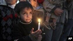 ایک فلسطینی بچہ غزہ پر اسرائیلی حملے کی دوسری سالگرہ کے موقع پر پر امن احتجاجی جلسہ میں ایک شمع روشن کیے ہوئے۔.