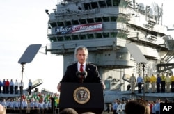 "FILE - Then-President George Bush declares the war over in Iraq, May 1, 2003. Behind him on board the carrier USS Abraham Lincoln is a banner reading: ""Mission Accomplished."""