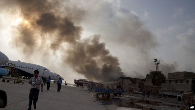 Smoke rises above the Jinnah International Airport where security forces continue to battle militants, June 9, 2014, in Karachi, Pakistan.