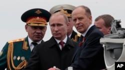 Ảnh tư liệu - Tổng thống Nga Vladimir Putin (giữa) và Bộ trưởng Quốc phòng Sergei Shoigu (trái), Trưởng ban An ninh Liên bang Alexander Bortnikov (phải) sau khi duyệt đội tàu chiến trong buổi diễu hành hải quân đánh dấu Ngày Chiến thắng ở Sevastopol, Crimea, ngày 9 tháng 5 năm 2014.