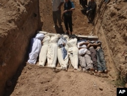 An image purports to show several bodies being buried near Damascus, Syria, around the time of an alleged chemical attack on one of its suburbs, Aug. 21, 2013.