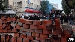 Tunus Başbakanı Gannuşi, istifa açıklamasını polis geçici hükümetin çekilmesini isteyen yüzlerce göstericiyi göz yaşartıcı bomba atarak dağıtmaya çalışırken yaptı