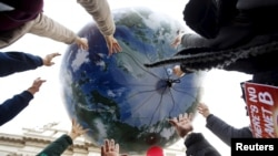 Protesters throw up a globe-shaped balloon during a rally held the day before the start of the 2015 Paris World Climate Change Conference, known as the COP21 summit, in Rome, Italy, November 29 2015.