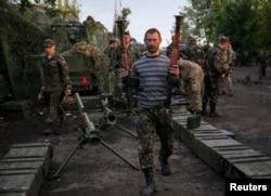 Ukrainian servicemen carry weapons, seized from pro-Russian separatists, near Slaviansk, July 8, 2014.