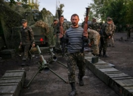 Ukrainian servicemen carry weapons, seized from pro-Russian separatists, near Slaviansk, July 8, 2014.