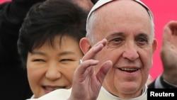 14일 한국 서울공항에 도착한 프란치스코 교황(오른쪽)이 환영객들을 향해 손을 흔들고 있다. 뒤쪽은 박근혜 한국 대통령.