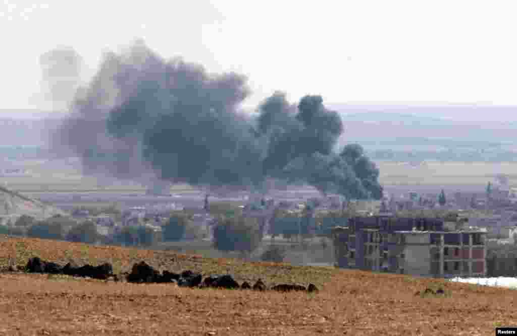 Suriyaning Turkiya chegarasi yaqinidagi Kobani shahridan quyuq qora tutun chiqmoqda, 6-oktabr, 2014-yil.