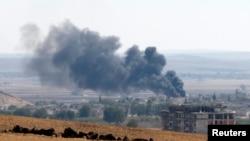 Asap mengepul akibat pertempuran di kota Kobani, terlihat dari Mursitpinar dekat kota Suruc, perbatasan Turki dengan Suriah (6/10).