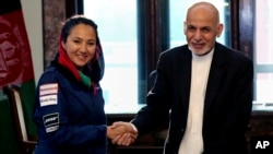 In this Monday, July 10, 2017 photo, Afghan President Ashraf Ghani shakes hands with Afghan-American female pilot Shaesta Waiz at the Presidential Palace in Kabul, Afghanistan.