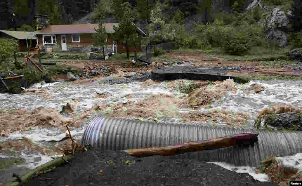 A home is stranded after a flash flood in Coal Creek destroyed the bridge near Golden, Colorado, Sept. 12, 2013.