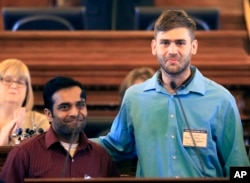 FILE - Alok Madasani (left) and Ian Grillot embrace after they were honored by the Kansas House of Representatives in Topeka, Kan. Adam Purinton was indicted by a federal grand jury, June 9, 2107, for a shooting in a suburban Kansas City bar. Srinivas Kuchibhotla was killed and his friend Alok Madasani was injured along with Ian Grillot, who intervened.