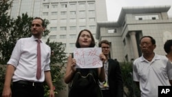 "Li Wenzu, center, wife of imprisoned lawyer Wang Quanzhang, holds a paper that reads ""Release Liu Ermin"" as she and supporters of a prominent Chinese human rights lawyer and activists stage a protest outside the Tianjin No. 2 Intermediate People's Court in Tianjin, China on Aug. 1, 2016."