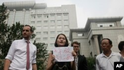 """FILE - Li Wenzu, center, wife of imprisoned lawyer Wang Quanzhang, holds a paper that reads """"Release Liu Ermin"""" as she and supporters of a prominent Chinese human rights lawyer and activists stage a protest outside the Tianjin No. 2 Intermediate People's Court."""