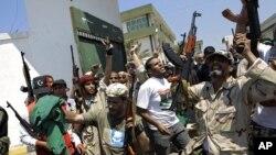 Des rebelles devant une base militaire pour femmes, à Tripoli (22 août 2011)