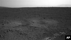 ພາຍຮອຍລໍ້ຂອງຍານ Curiosity ຢູ່ເທິງດາວພະອັງຄານ ຫລັງຈາກທີ່NASA ບັງຄັບໃຫ້ຍານແລ່ນອອກສໍາຫລວດ ໃນມື້ນີ້, ວັນທີ 22 ສິງຫາ 2012.