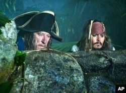 Captain Sparrow (Johnny Depp, right) and Hector Barbossa (Geoffrey Rush) spy on a Spanish encampment during the search for the legendary Fountain of Youth.