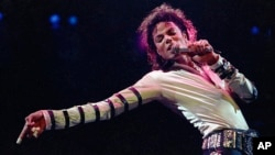 FILE - Michael Jackson leans, points and sings, dances and struts during the opening performance of his 13-city U.S. tour, in Kansas City, Missouri.