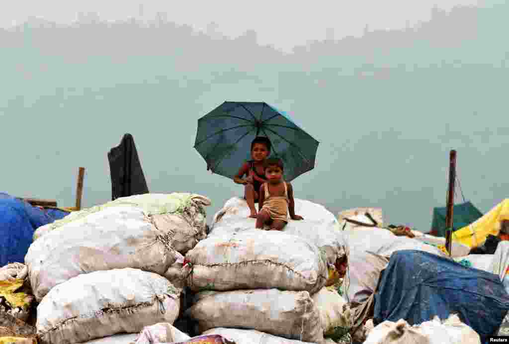 Children sit on sacks filled with recyclable material at a garbage dumping site in Guwahati, India.