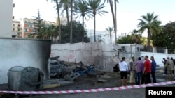 Onlookers and security personnel stand at the scene of a car bomb explosion near the Egyptian embassy in the Libyan capital of Tripoli Nov. 13, 2014. (Reuters)