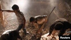 Tim penyelamat berupaya mencari korban di antara reruntuhan bangunan di desa Varzaghan, selatan Azarbaijan (11/8). Korban tewas mencapai lebih dari 300 orang tewas dan 3.000 orang cedera.