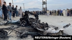 Afghanistan, Kabul, People stand at the site of a blast