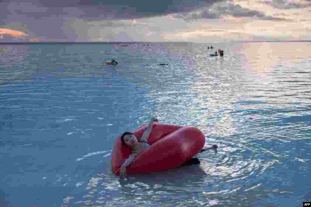 A woman uses a float at the Tumon bay area of Guam.