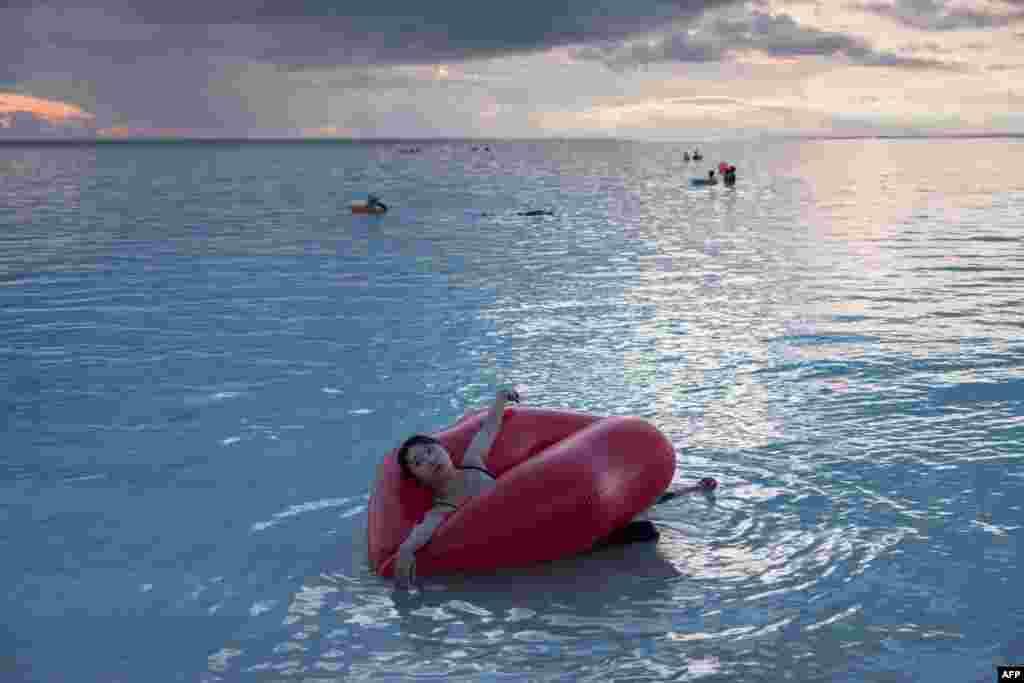 Guam adası Tumon koyunda bir kadın lastik bir botla denize açılmış . Guam Valiliği Kuzey Kore'nin adaya füze fırlatma tehdidinin adanın turizmini etkilemediğini açık aldı.