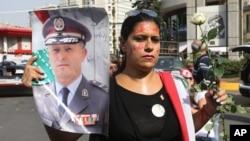 Libanka nosi sliku generala Ašrafa Rifija dan posle bombaškog napada u kojem je u Bejrutu ubijen general Visam al-Hasan i još najmanje sedam osoba