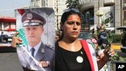 Một phụ nữ Li Băng cầm ảnh của Ðại tướng tư lệnh các lực lượng nội an Li Băng Ashraf Rifi tại một cuộc biểu tình ở Achrafieh, một ngày sau vụ đánh bom giết chết Cục trưởng tình báo Wissam al-Hassan và ít nhất 7 người khác ở Beirut.