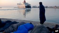 Izbeglica iz Pakistana pored migranata koji spavaju posmatra kako brod odlazi iz luke sa grčkog ostrva Hios, 6. april 2016.