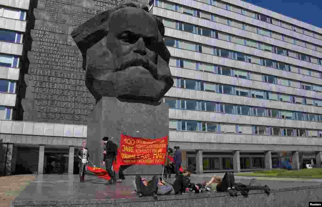 """2018年5月1日,在德国开姆尼茨,左翼活动分子举行针对德国极右派的示威抗议后,在马克思像脚下休息。德国总统施泰因迈尔在四川大学的演讲稿说,马克思无疑是一个了不起的德国知识分子,一个哲学家,经济、历史和社会学家,""""是一个激昂的人道主义者。他要求有新闻自由,人道的工作环境,妇女的政治权利和环境保护。"""""""