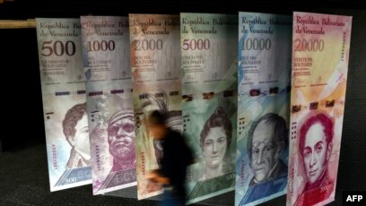 A Man Walks Past Banners Showing Depicting Venezuela S Currency The Bolivar At