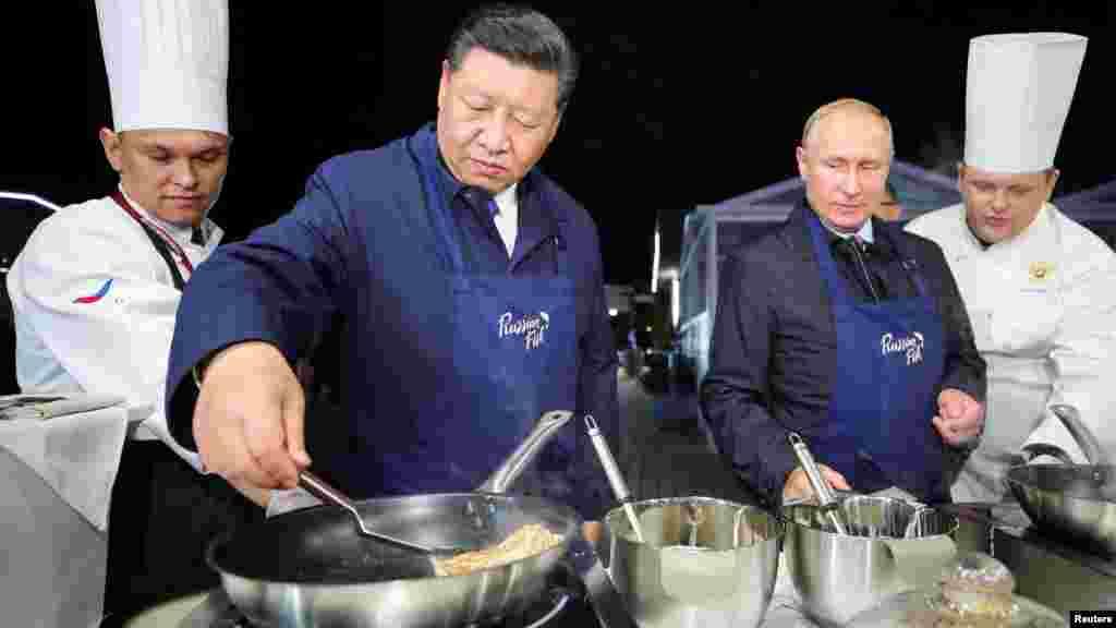 俄罗斯总统弗拉基米尔·普京和中国国家主席习近平2018年9月11日在俄罗斯符拉迪沃斯托克的东方经济论坛期间参观远东街展览,习近平摊煎饼——俄罗斯煎饼。在俄罗斯因为干预美国选举问题而同美国关系紧张之际,在中国与美国由于贸易争端而关系紧张之际,在俄罗斯符拉迪沃斯托克(又称海参崴)举行了东方经济论坛,俄中领导人在论坛期间举行了今年第三次会晤,加强两国合作关系。