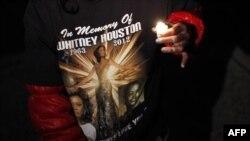 Một người hâm mộ, đứng bên ngoài nhà quàn ở Newark, New Jersey, mặc chiếc áo có in hình ca sĩ Whitney Houston